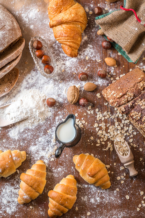 På bagerit mjölkar stilleben med mini- giffel, bröd, muttrar och mjöl royaltyfri foto