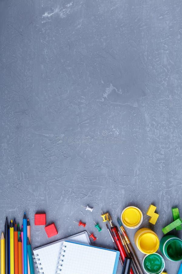 På bakgrunden med ett ställe för den längst ner inskriften orienteringen av brevpapper, färger, blyertspennor och anteckningsböck royaltyfria foton