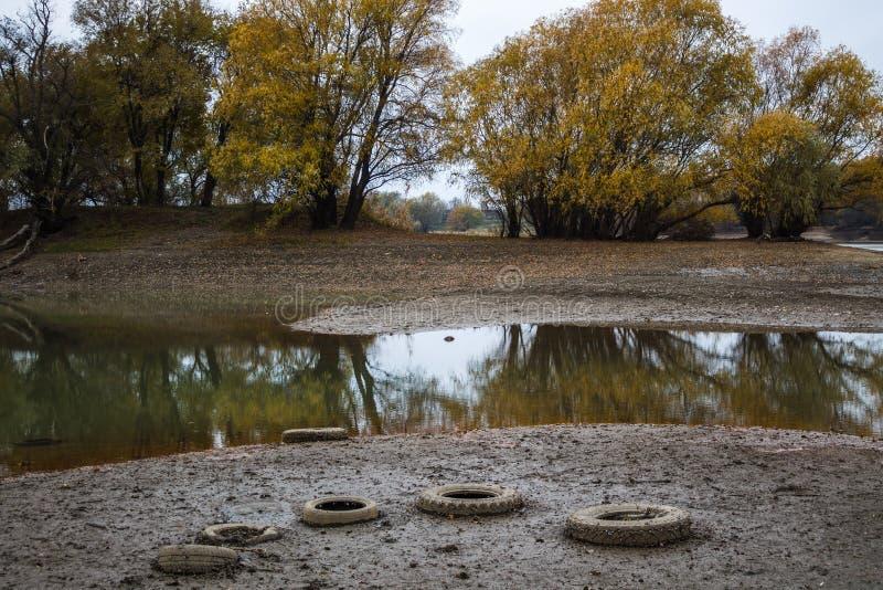 På bankerna av floden är bilgummihjul ekologisk milj?fotof?rorening f?r kris fotografering för bildbyråer