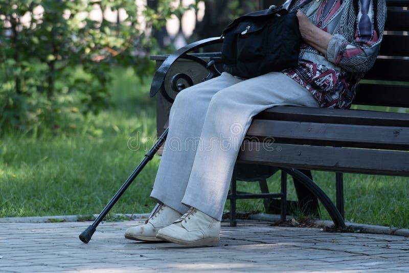 På bilden av en fot, en krycka och en bänk i parkera royaltyfri fotografi