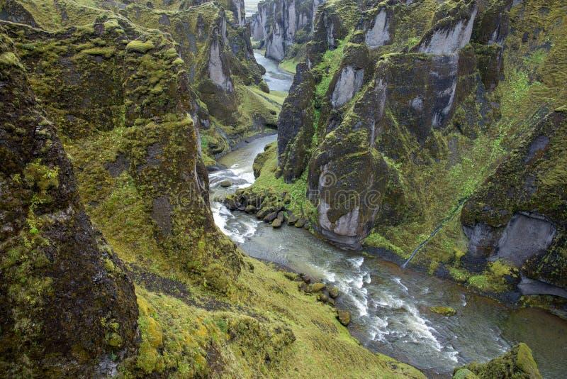 På botten av en djup pittoresk kanjon är turbulenta slingrande flöden för en flod, lutningarna bevuxna med mossa arkivfoto