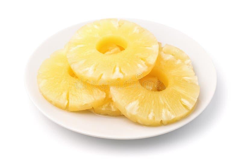 På burk ananasskivor på plattan arkivfoto