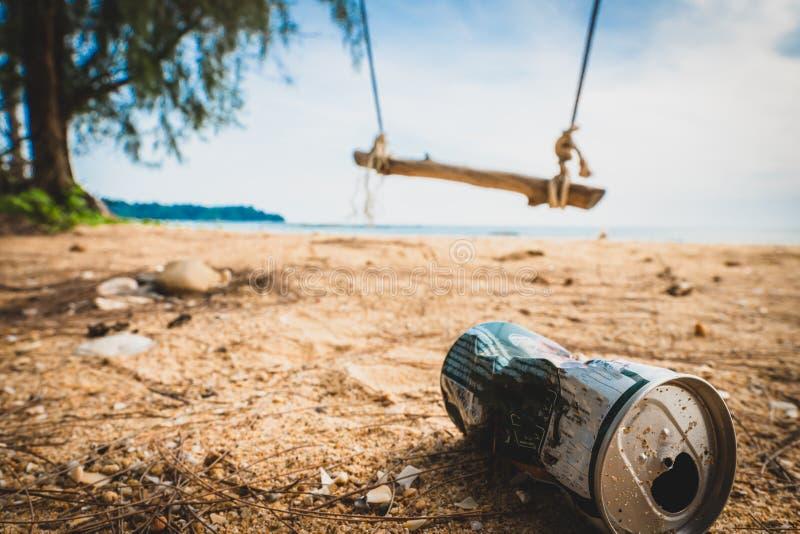 På burk på stranden förstör miljön Avskräde i sanden på naturen avfall på på en härlig strand med en gunga arkivbild