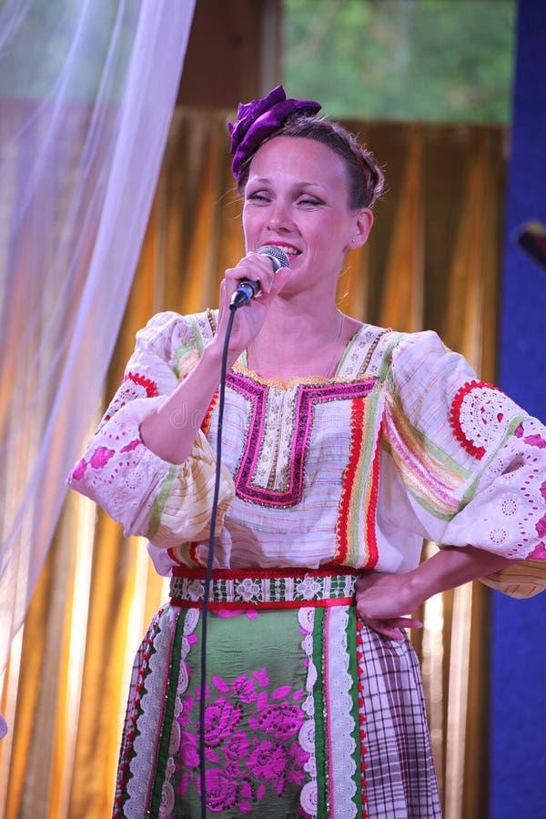 På de härliga flickorna för etapp i nationella ryska dräkter kappasundresses med vibrerande broderi - folkmusikgrupp hjulet arkivbild