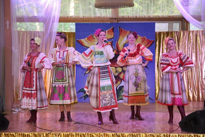 På de härliga flickorna för etapp i nationella ryska dräkter kappasundresses med vibrerande broderi - folkmusikgrupp hjulet royaltyfria foton