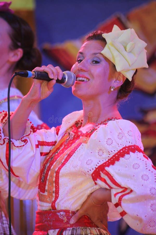 På de härliga flickorna för etapp i nationella ryska dräkter kappasundresses med vibrerande broderi - folkmusikgrupp hjulet royaltyfria bilder