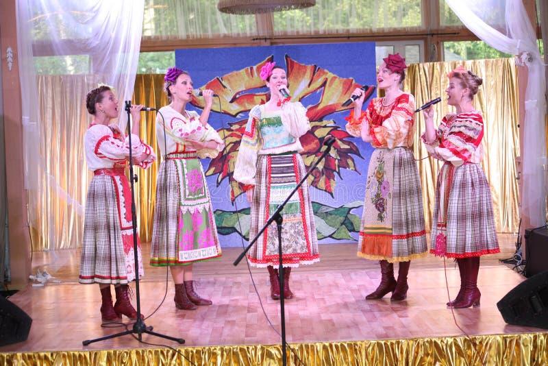 På de härliga flickorna för etapp i nationella ryska dräkter kappasundresses med vibrerande broderi - folkmusikgrupp hjulet arkivfoton