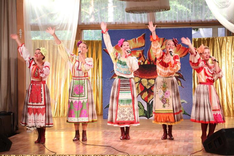 På de härliga flickorna för etapp i nationella ryska dräkter kappasundresses med vibrerande broderi - folkmusikgrupp hjulet royaltyfri bild