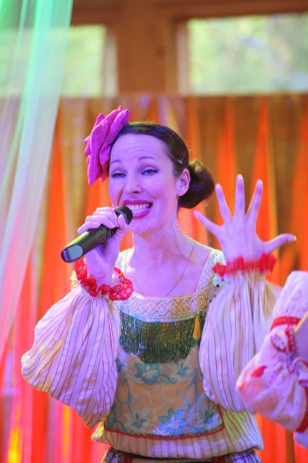 På de härliga flickorna för etapp i nationella ryska dräkter kappasundresses med vibrerande broderi - folkmusikgrupp hjulet fotografering för bildbyråer