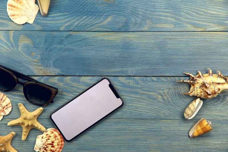 På den blåa träbakgrunden på vänstersidan är solglasögon, en telefon, och olika skal, på rätten är tre snäckskal arkivbilder