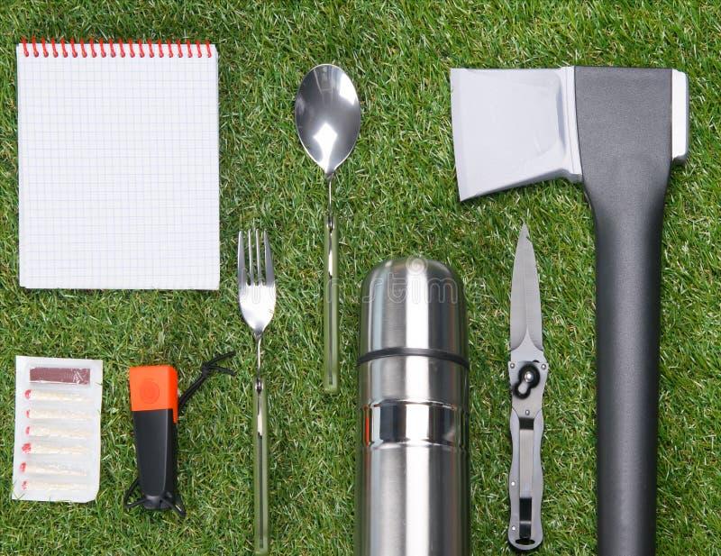 På den gröna gräsmattan lade trevligt ut objekt för lös utomhus- rekreation, matcher, yxa, termos, gaffel, sked, ficklampa, kniv  fotografering för bildbyråer