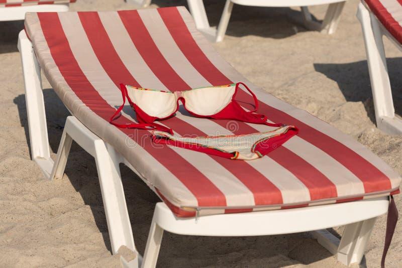 På en deckchair är en röd baddräkt, närbilden, ett begrepp av avkoppling royaltyfri foto