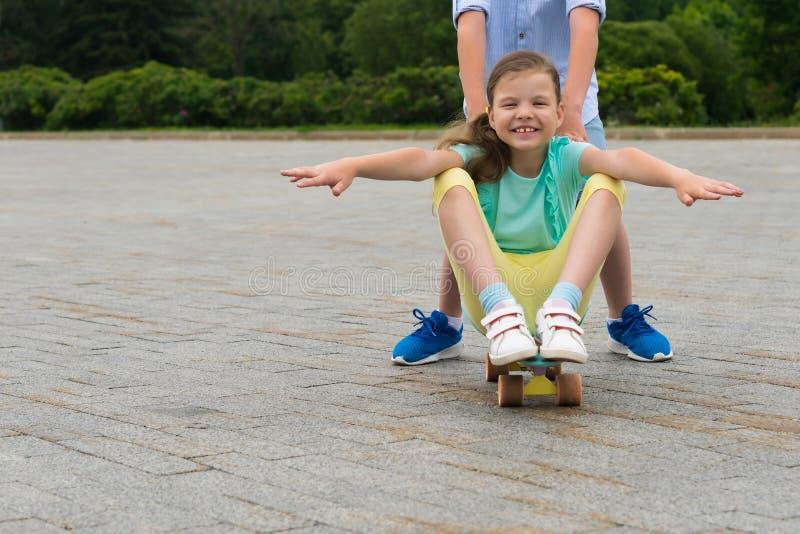 På en gå i parkera skjuter pojken en flicka framme av honom, som sitter på en skateboard royaltyfri foto