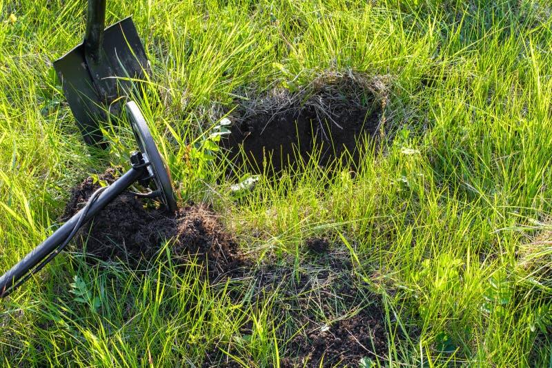 På en grön äng med gräs som kastas en metalldetektor och en skyffel royaltyfri foto