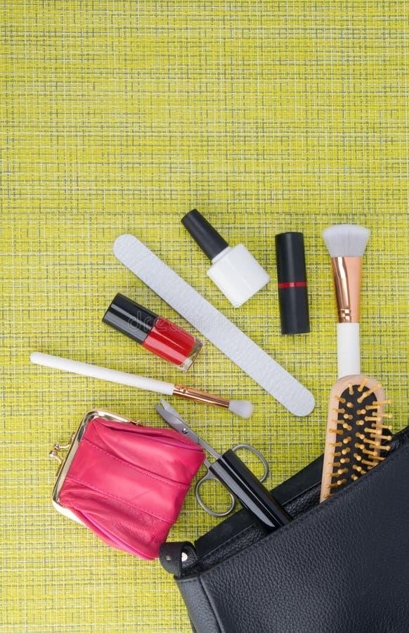 På en grön bakgrund ligger spikar en svart kosmetolog, bredvid spridda apparater för manikyr, polermedel, läppstift, pulverborste arkivbild