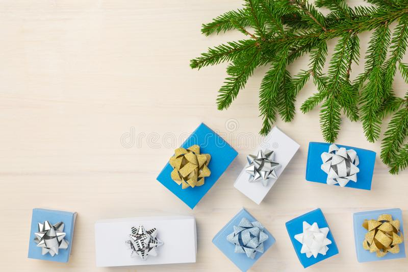 På en ljus träbakgrund är granfilialer Närliggande är små gåvaaskar som dekoreras med, försilvrar och guld- pilbågar kopia arkivbilder