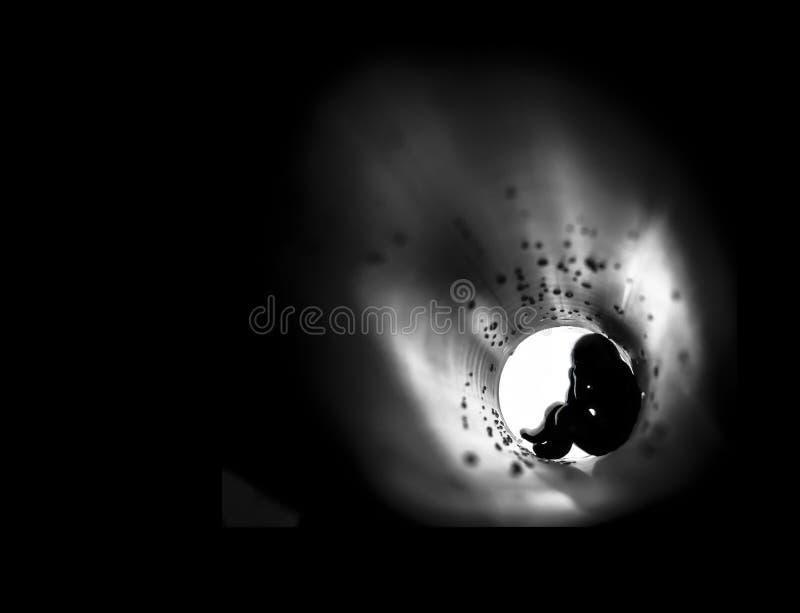 På en mörk fyrkantig bakgrund i mitten av en rund ström av ljusa trumpetdroppar sitter mannen rädd fobi royaltyfria bilder
