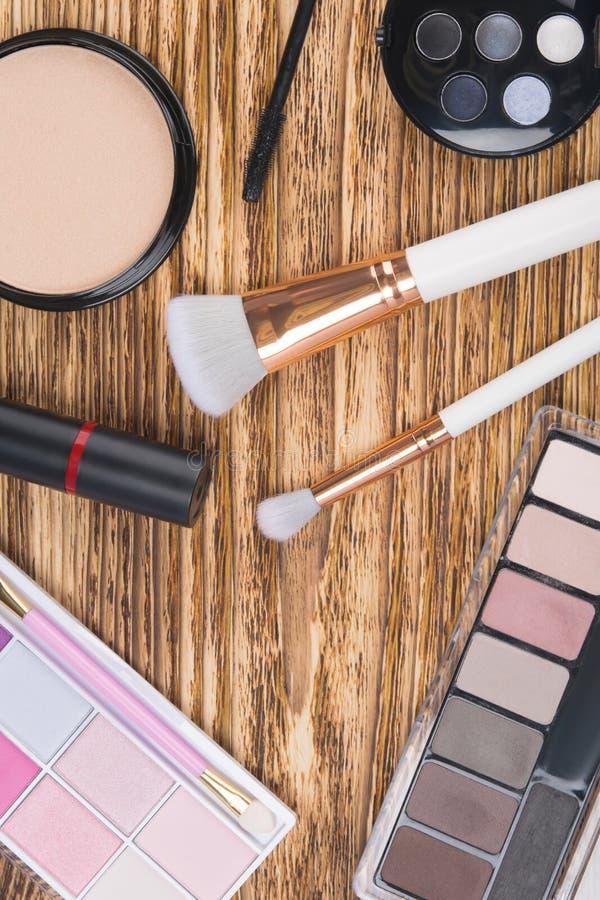 På en mörk träbakgrund, objekt för makeup, borstar, pulver, kulöra skuggor, läppstift och mascara royaltyfri bild