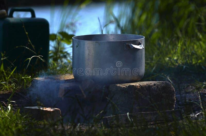 På en picknick nära floden en stor metallpanna som fisksoppa förbereds i mot bakgrunden av grönt gräs och rök royaltyfri fotografi