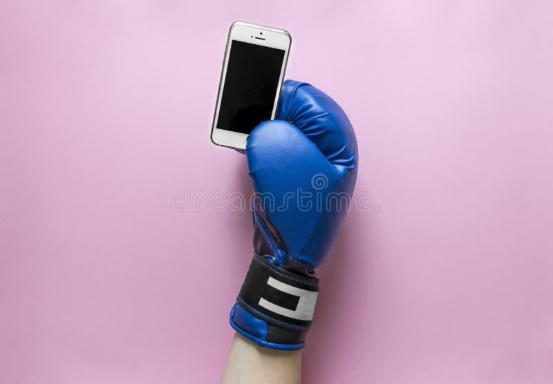 På en rosa bakgrund färgar en hand i en boxninghandske av blått med en telefon i händer royaltyfri fotografi