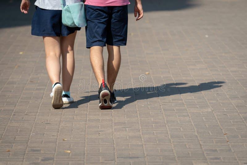 På en solig dag promenerar ett par av folk trottoaren De mänskliga skuggorna är synliga på trottoaren tillbaka sikt arkivbild