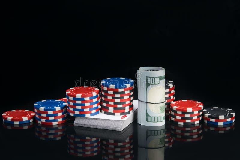 På en svart bakgrund med en reflexion, en pyramid av pokerchiper och hundra dollarräkningar som är hoprullade på en kortlek arkivfoto