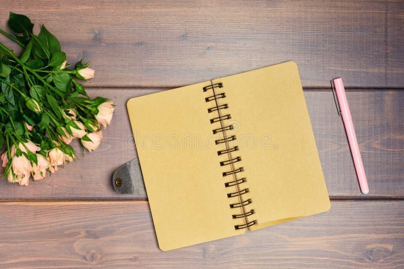 På en tabell som göras av naturliga träplankor, ligger en bukett av små sprejrosor och en tom öppen svart anmärkning kopiera avst fotografering för bildbyråer