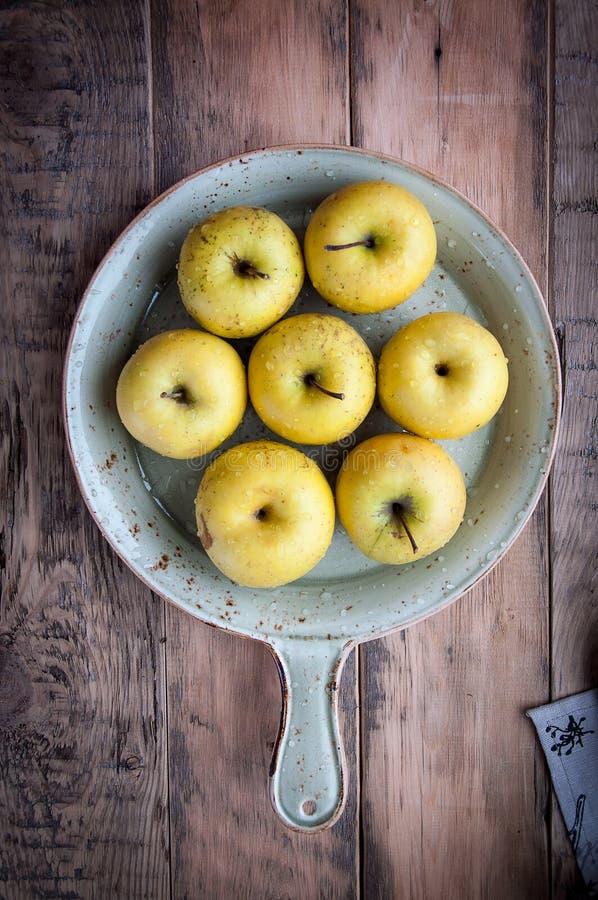 På en träbakgrund på nya äpplen för ett uppläggningsfat med vattensmå droppar arkivfoto