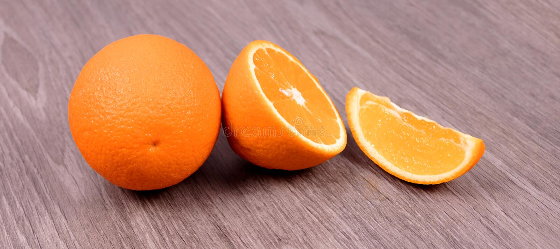 P? en tr?bakgrundsapelsin, halva en apelsin och en skiva arkivbild