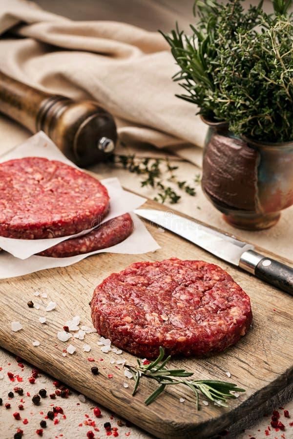 På en träskärbräda på kraft papper finns det rå nötkötthamburgare för hamburgare, kryddor, rosmarin, en peppar maler, a arkivbild