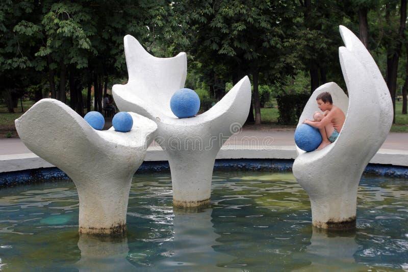 På en varm dag badar pojken i pölen av Centralet Park royaltyfri foto