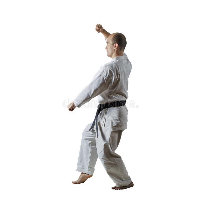 På en vit isolerad bakgrund med ett svart bälte gör en idrottsman nen formella karateövningar royaltyfri bild