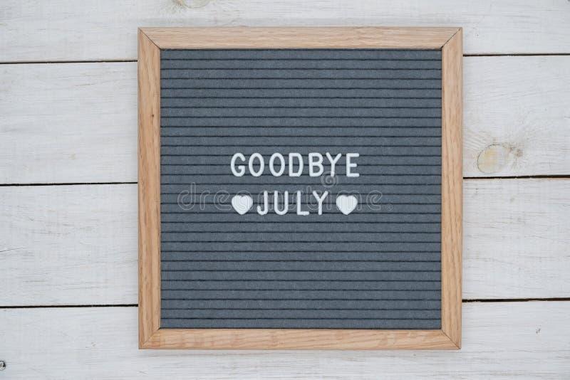 På engelska farväl Juli för text och ett hjärtatecken på ett grått klätt med filt bräde i en träram arkivfoton