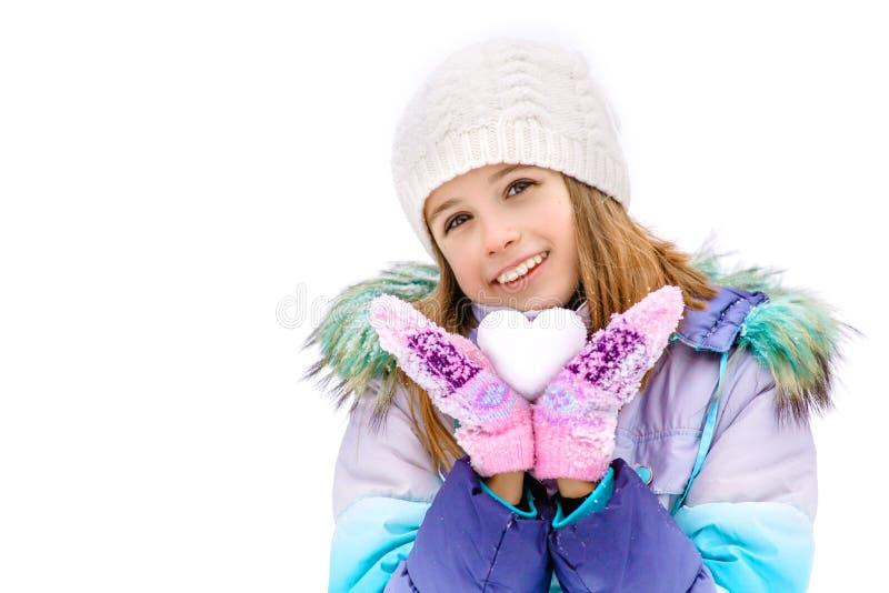 På ett innehav för flicka för dag för vinter` s i händer kasta snöboll i formen av en hjärta Flickaanseende på ett vitt snöomslag arkivfoto