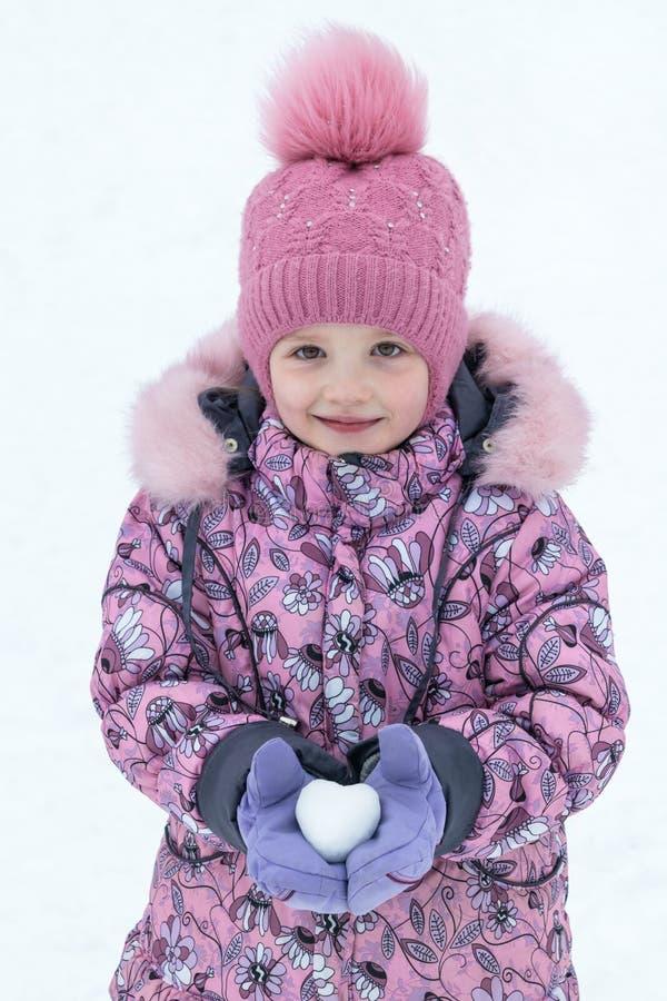 På ett innehav för flicka för dag för vinter` s i händer kasta snöboll i formen av arkivfoto