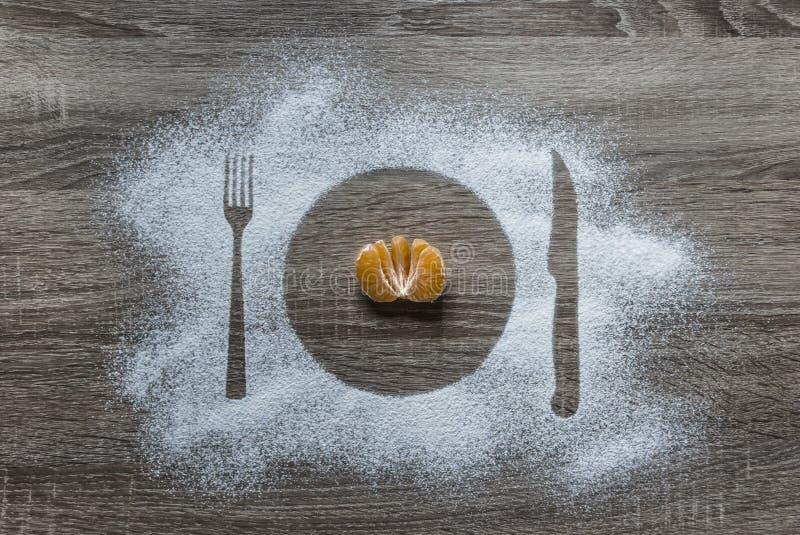 På ett träbakgrundsmjölpulver pudrad mandarin för lögner för anordningar för kniv för gaffel för platta för snökonturplatta halv  arkivbilder