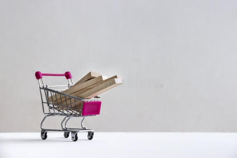 På ett vitt golv på en vit bakgrund finns det en shoppingspårvagn med träkvarter av bräden fotografering för bildbyråer