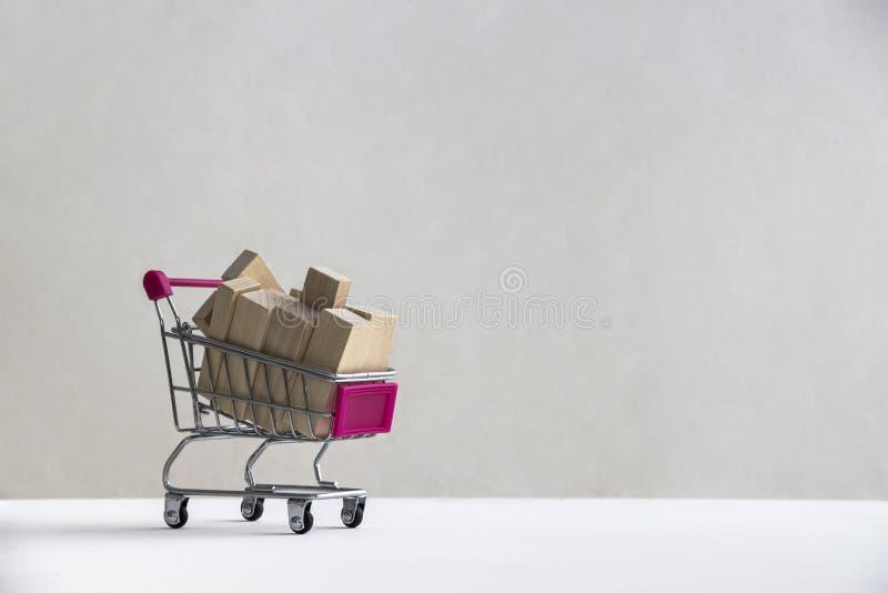 På ett vitt golv på en vit bakgrund finns det en shoppingspårvagn med träkvarter av bräden royaltyfri foto