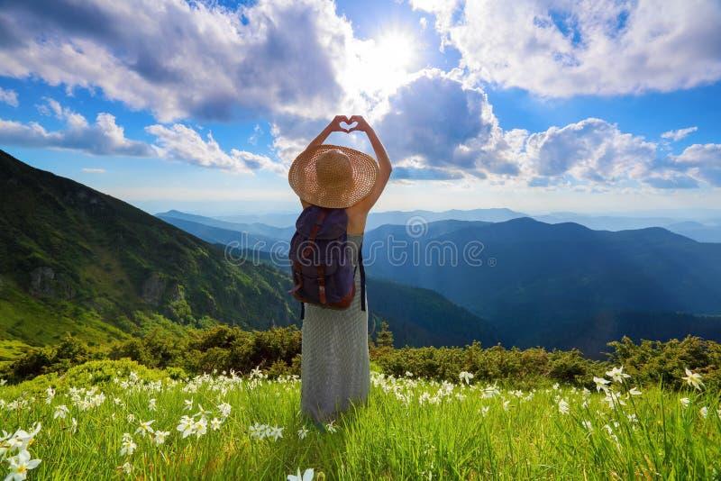 På gräsmattan av vita blommor blir hipsterflickan i den långa klänningen, sugrörhatt med den tillbaka säcken som tycker om solned fotografering för bildbyråer