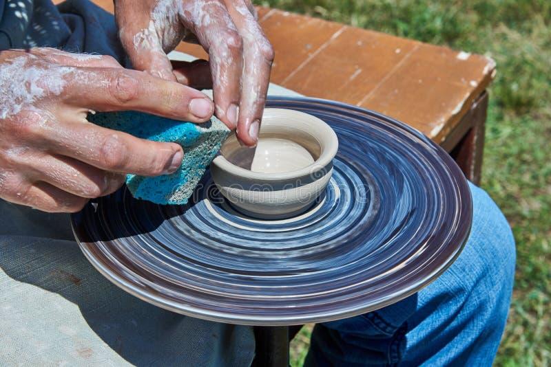 På hjulet för keramiker` s finns det en lerakopp royaltyfri foto