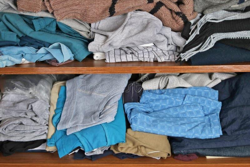 På hyllorna av garderoben för man` s finns det alltid kaos och c arkivbild