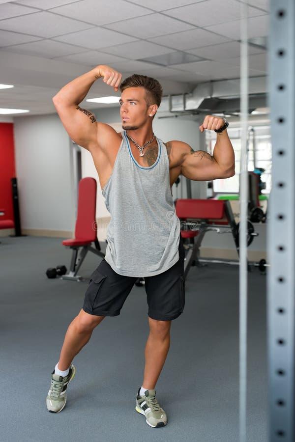 På idrottshallen Stilig idrottsman nen som poserar visa hans biceps royaltyfri foto