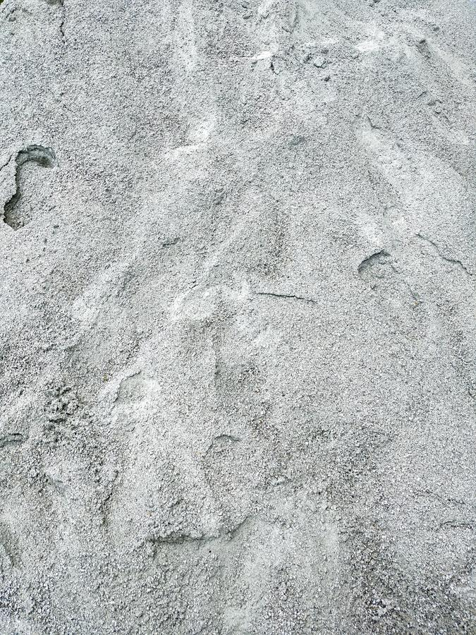 På jordningen lägga en hög av grå sand Massen är ojämn, smutsigt, med spårar på yttersidan royaltyfri bild