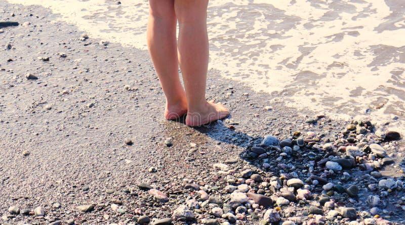 På kanten av havet kvinnans lägger benen på ryggen fot/med havet som sveper försiktigt dem royaltyfria foton