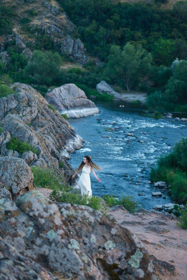 På klippan står en härlig flicka i en vit klänning med dreadlocks Mot bakgrunden av den snabba och turbulenta floden royaltyfri foto