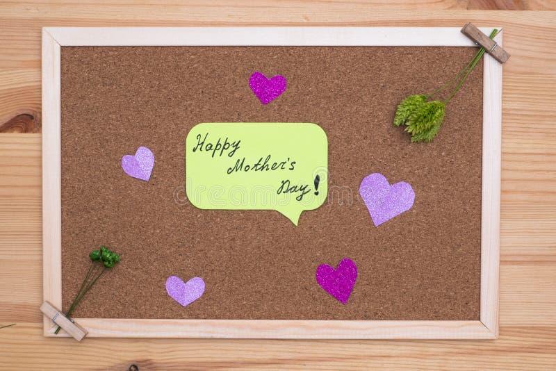 På korkbrädet med klistermärkear med lyckliga moders för inskrift dag runt om hjärtorna och de gröna blommorna arkivfoto