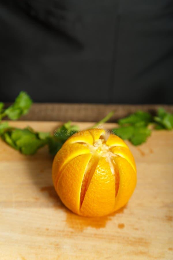På lögner för ett träbräde en apelsin och sidor av grönska royaltyfri fotografi