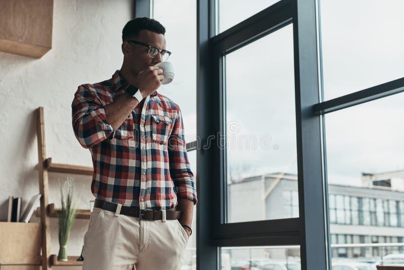 På lite avbrott Stilig ung man som dricker kaffe och keepin royaltyfri foto