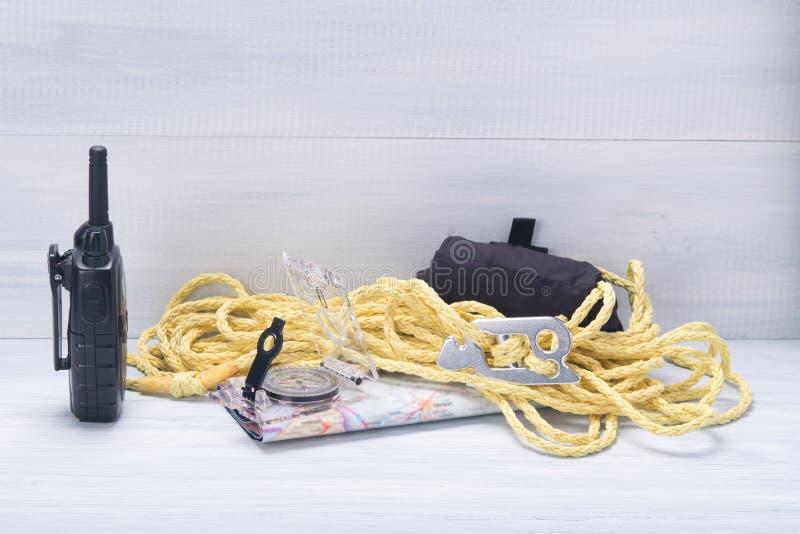 På ljust - grått bakgrund, handelsresandeuppsättning, walkietalkie, kompass, översikt och rep arkivbilder