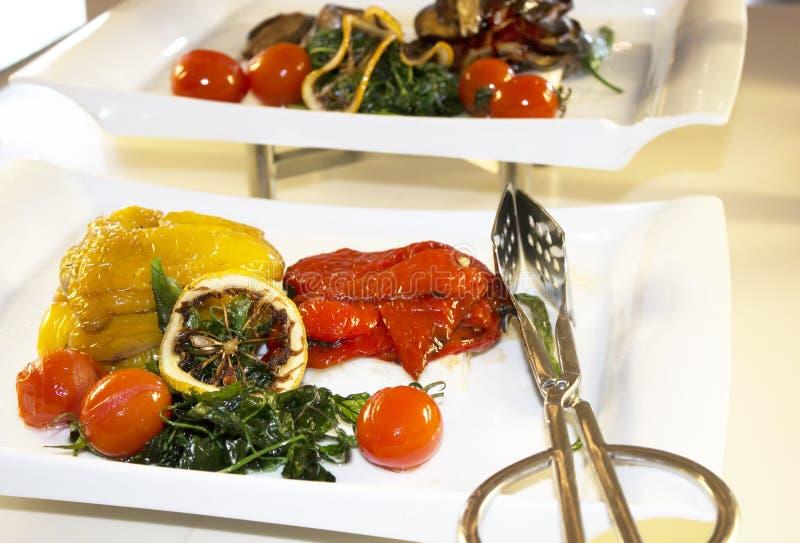 På magasinet fodrade med röda och gula grillade peppar, i foen royaltyfri fotografi